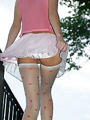 31 pictures - White skirt of gal in stockings hardly covering her upskirt
